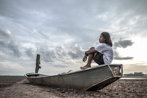 Le donne si siedono abbracciando le ginocchia su una barca da pesca e guardano il cielo sulla terra ferma e il riscaldamento globale Foto Gratuite