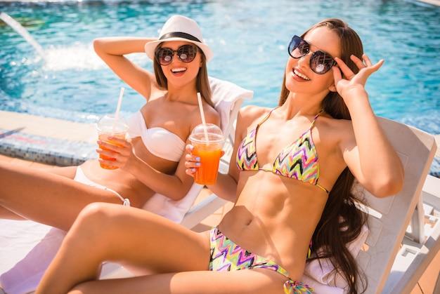 Le donne sono sdraiate su chaise-longue e bevono cocktail. Foto Premium