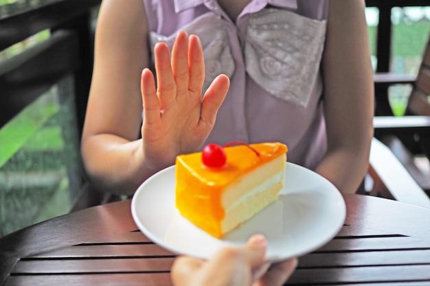 Le donne stanno perdendo peso. scegli di non avere un piatto di torta che gli amici mandano. Foto Premium