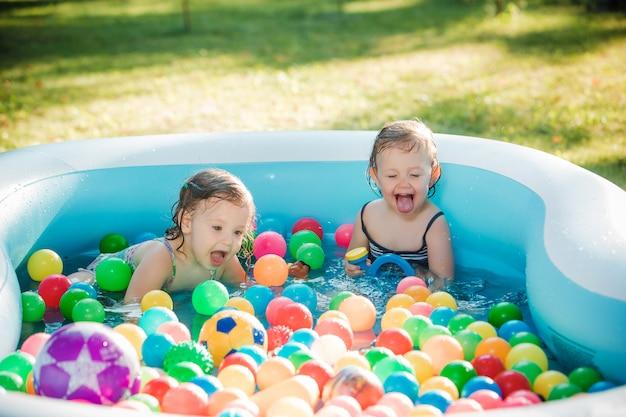 Le due bambine di due anni che giocano con i giocattoli in piscina gonfiabile nella giornata di sole estivo Foto Gratuite