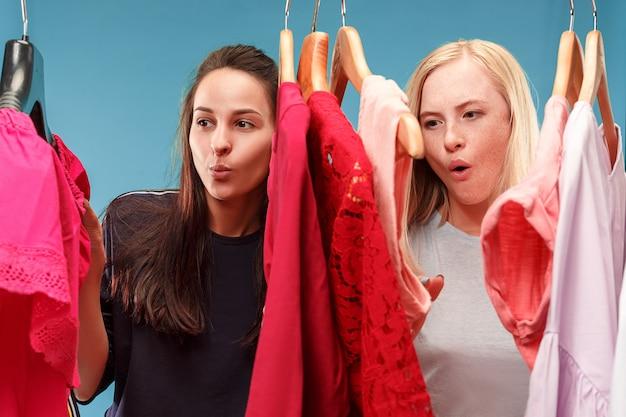 Le due giovani belle ragazze guardano i vestiti e provano mentre scelgono in negozio Foto Gratuite