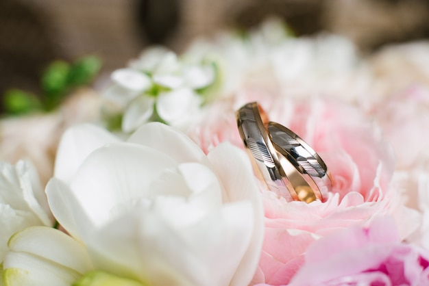 Le fedi nuziali in fiori delicati di nozze si chiudono su Foto Premium