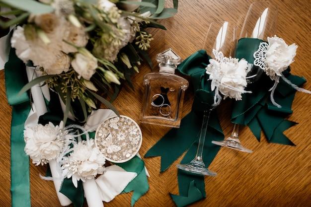 Le fedi nuziali si trovano sulla bottiglia di profumo vicino ai fiori Foto Gratuite