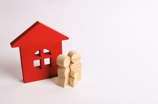 Le figure della gente stanno vicino ad una casa di legno. una giovane famiglia è in piedi vicino a casa loro. Foto Premium
