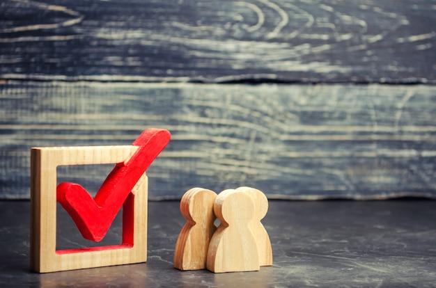 Le figure umane in legno stanno insieme accanto a un segno di spunta nella casella. il concetto di elezioni Foto Premium
