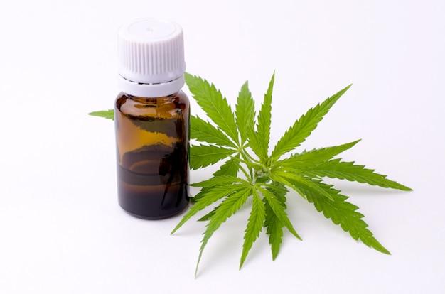 Le foglie di cannabis e la cannabis estraggono l'olio nella bottiglia. Foto Premium