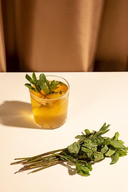 Le foglie di menta con il cocktail bevono il vetro sulla tavola bianca Foto Gratuite