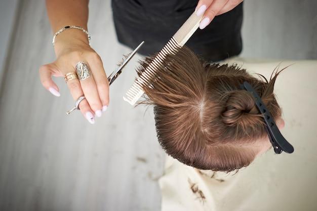 Le forbici tagliano i capelli delle ragazze nel salone di bellezza, donna rossa. Foto Premium