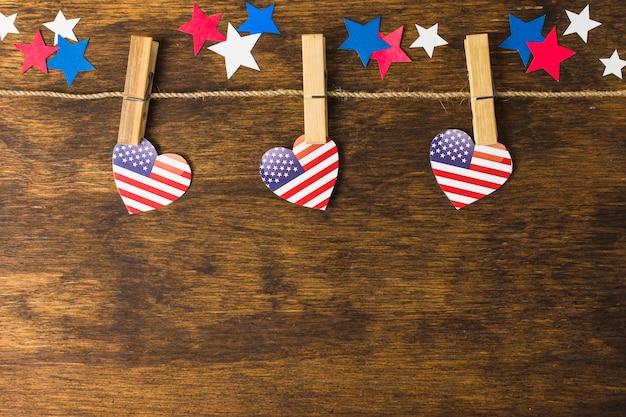 Le forme del cuore della bandiera americana degli sua appendono sulle mollette da bucato decorate con le stelle sullo scrittorio di legno Foto Gratuite