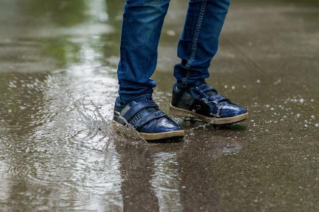 Le gambe del bambino in primo piano delle scarpe da tennis, il bambino salta in pozzanghere. salute, concetto di infanzia felice. Foto Premium