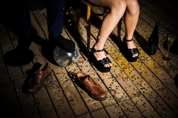 Le gambe della donna in scarpe vicino alla gamba dell'uomo sulla palla da discoteca vicino agli stivali Foto Gratuite