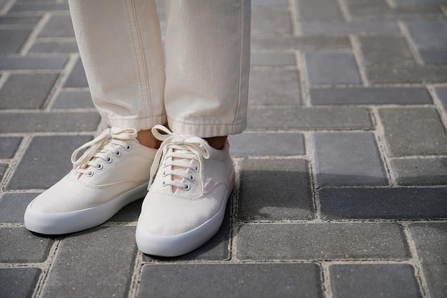 Le gambe della ragazza in nuove scarpe da ginnastica bianche e jeans Foto Premium
