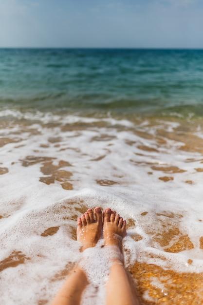 Le gambe della ragazza nell'acqua di mare sulla riva sabbiosa Foto Premium