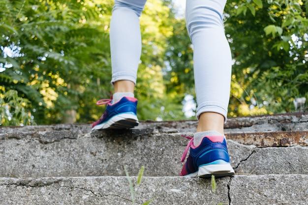 Le gambe femminili in scarpe da ginnastica e jeans salgono le scale di cemento nel parco Foto Premium