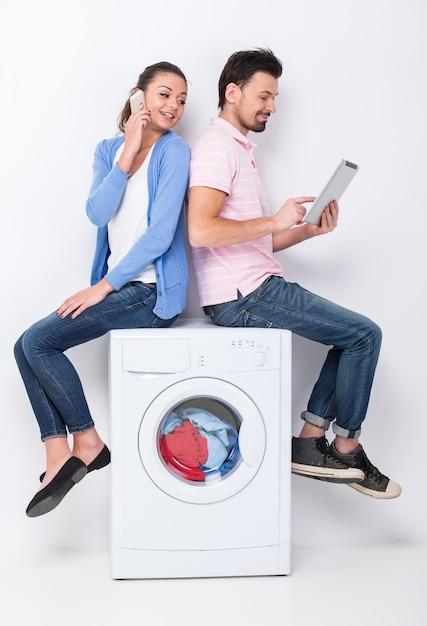 Le giovani belle coppie stanno utilizzando il computer portatile e il telefono cellulare. Foto Premium