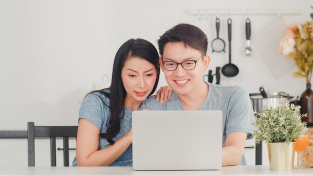 Le giovani coppie asiatiche godono di di acquistare online sul computer portatile a casa. stile di vita giovane marito e moglie felice di acquistare e-commerce dopo aver fatto colazione in cucina moderna a casa la mattina. Foto Gratuite