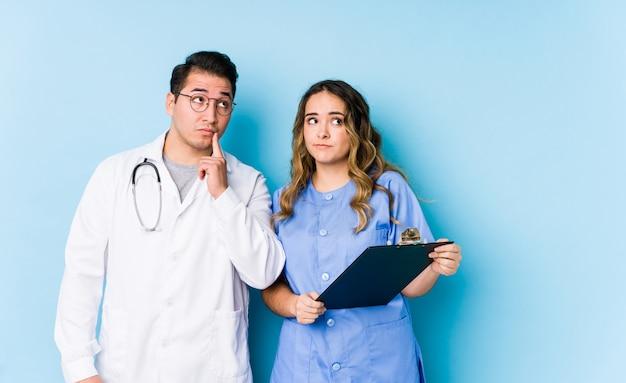 Le giovani coppie di medico che posano in una parete blu hanno isolato lo sguardo lateralmente con l'espressione dubbiosa e scettica. Foto Premium