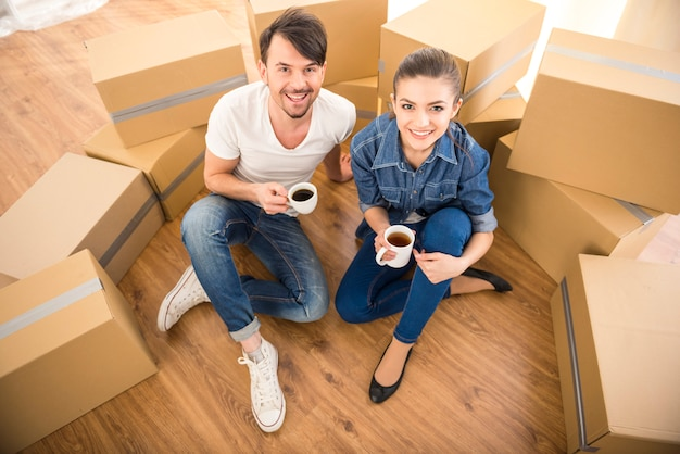 Le giovani coppie felici che bevono tè e caffè. Foto Premium
