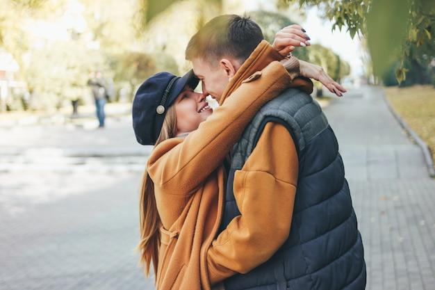 Le giovani coppie felici negli amici degli adolescenti di amore si sono vestite nello stile casuale che camminano insieme sulla via della città nella stagione fredda Foto Premium