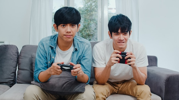 Le giovani coppie gay asiatiche giocano a casa, uomini teenager coreani lgbtq che utilizzano la leva di comando che ha momento felice divertente insieme sul sofà nel salone a casa. Foto Gratuite