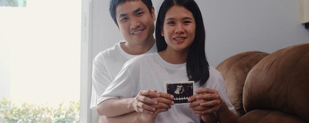 Le giovani coppie incinte asiatiche mostrano e guardando il bambino della foto di ultrasuono in pancia. mamma e papà sentirsi felici sorridenti pacifici mentre abbi cura del bambino sdraiato sul divano nel salotto di casa. Foto Gratuite