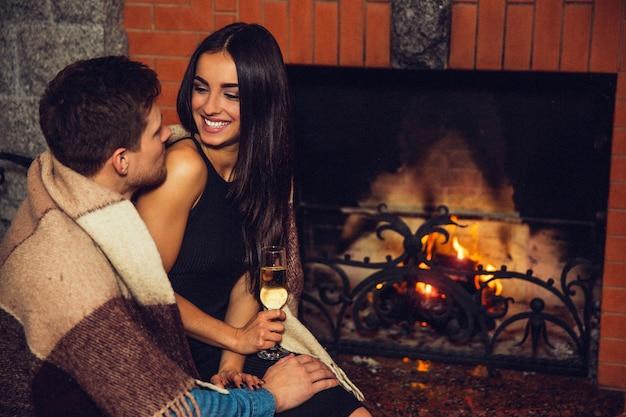 Le giovani donne allegre si siedono sul grembo dell'uomo e lo guardano. lei sorride. modello tenere bicchiere di alcol. si siedono nella stanza al camino. le spalle del ragazzo si coprono di coperta. Foto Premium