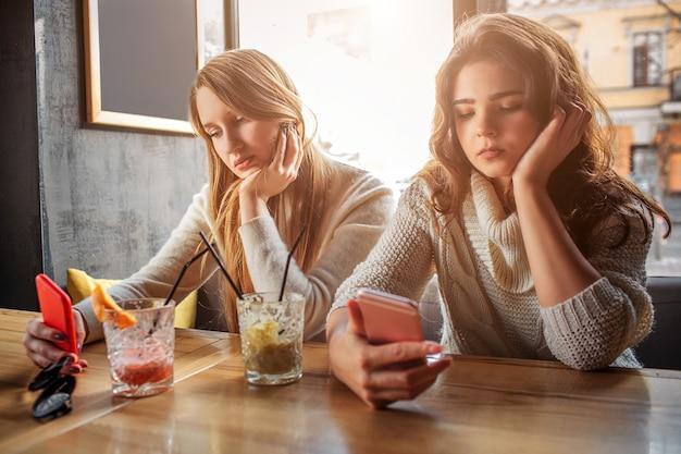 Le giovani donne annoiate si siedono al tavolo. tengono in mano i telefoni e lo guardano. i modelli hanno bicchieri con drink a tavola. Foto Premium