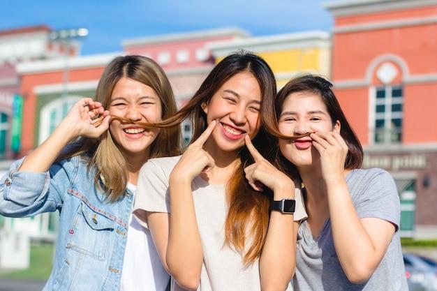 Le giovani donne asiatiche felici raggruppano lo stile di vita della città giocando e chiacchierando Foto Gratuite