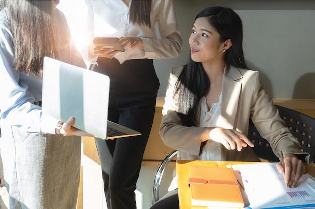 Le giovani donne di affari discutono la strategia dei grafici e il programma finanziario Foto Premium