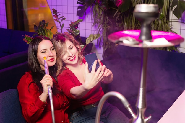 Le giovani donne in vestiti rossi fumano narghilè e prendono un selfie Foto Premium
