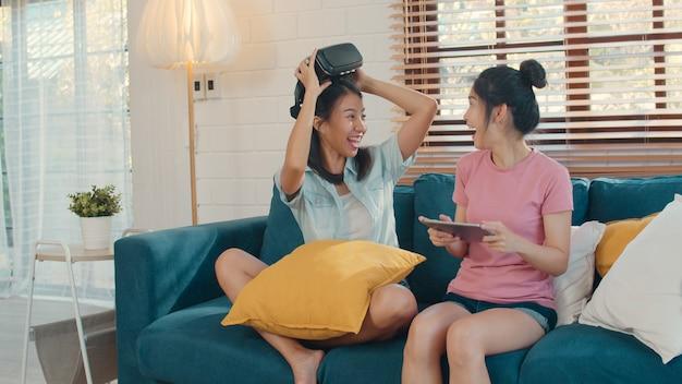 Le giovani donne lesbiche asiatiche del lgbtq si accoppiano facendo uso della compressa a casa Foto Gratuite