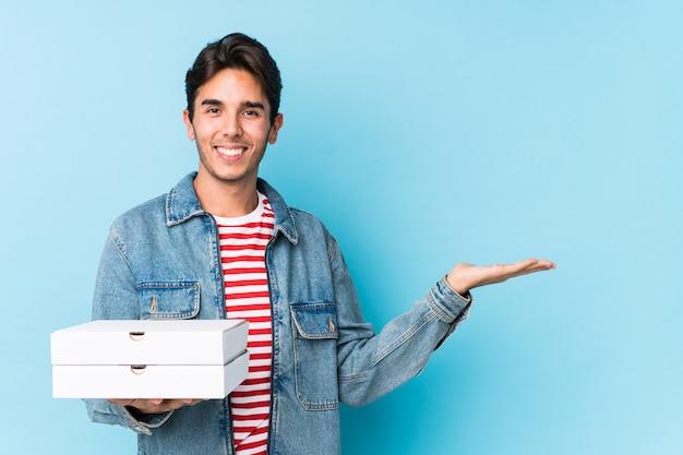 Le giovani pizze caucasiche della tenuta dell'uomo isolate hanno mostrato lo spazio di una copia su una palma e tengono un'altra mano sulla vita. Foto Premium