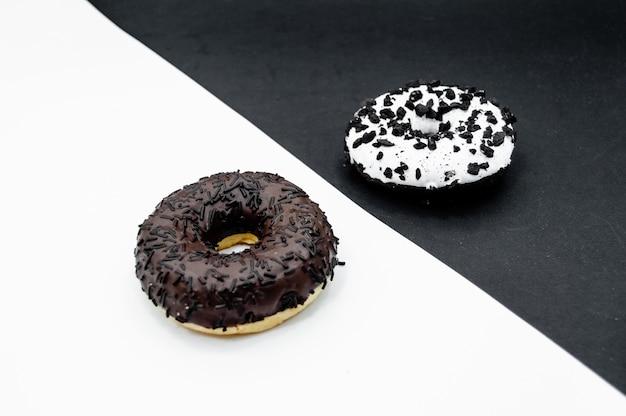 Le guarnizioni di gomma piuma con cioccolato lustrate con spruzza le guarnizioni di gomma piuma isolate su fondo astratto nero bianco Foto Premium