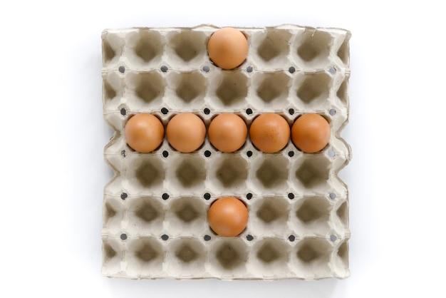Le lettere di numero organizzano dalle uova in vassoio su fondo bianco. Foto Premium
