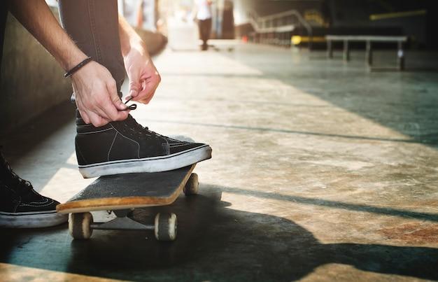 Le mani che legano le scarpe indossano uno skateboard Foto Gratuite