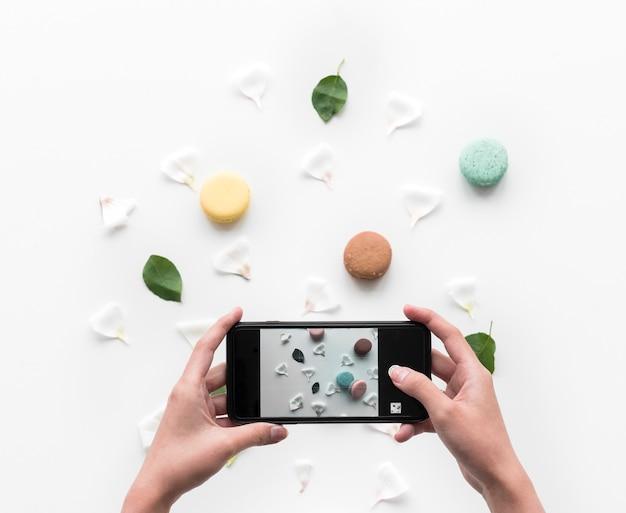 Le mani che tengono uno smart-phone catturano un amaretto Foto Gratuite