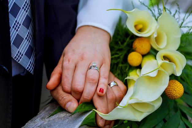Le mani con gli anelli di oro di nozze gli sposi felici ed i fiori del mazzo kala Foto Premium