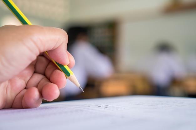 Le mani degli studenti che prendono gli esami, scrivendo la stanza dell'esame con la matita della tenuta sulla prova ottica Foto Premium