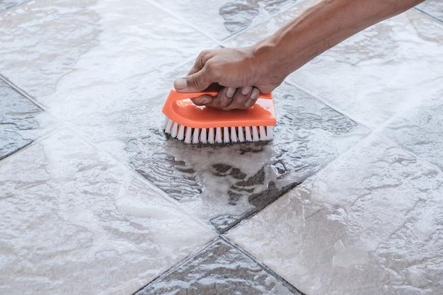 Le mani degli uomini vengono utilizzate per convertire la pulizia della lucidatura sul pavimento piastrellato. Foto Premium