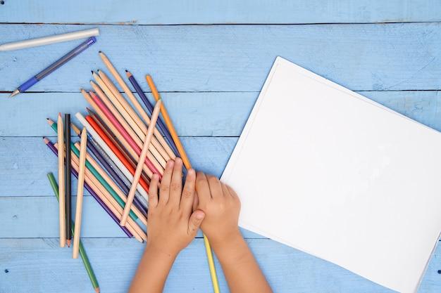 Le mani dei bambini disegnano con le matite nell'album sul tavolo blu Foto Premium