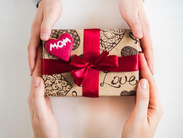 Le mani dei bambini e una scatola con un regalo Foto Premium