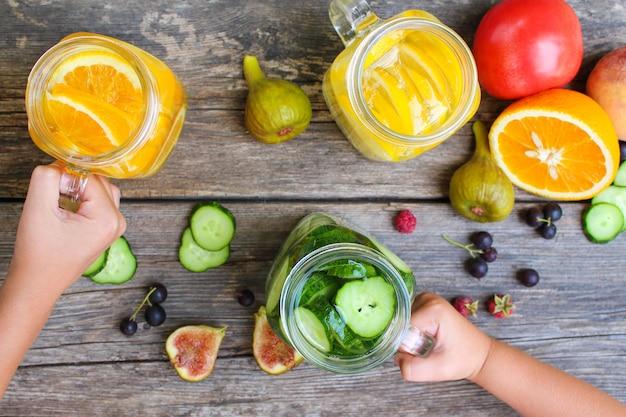 Le mani dei bambini prendono le bevande con fondo di frutta e verdura Foto Premium