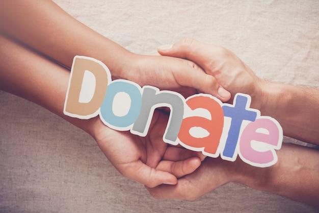 Le mani del bambino e dell'adulto che tengono la parola donano, donazione e concetto della carità Foto Premium