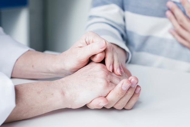 Le mani del dottore che tendono ad un paziente Foto Gratuite