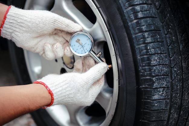 Le mani del meccanico controllano la pressione dell'aria del pneumatico Foto Premium