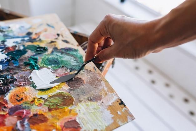 Le mani del pittore si chiudono su che mescolano le vernici Foto Gratuite