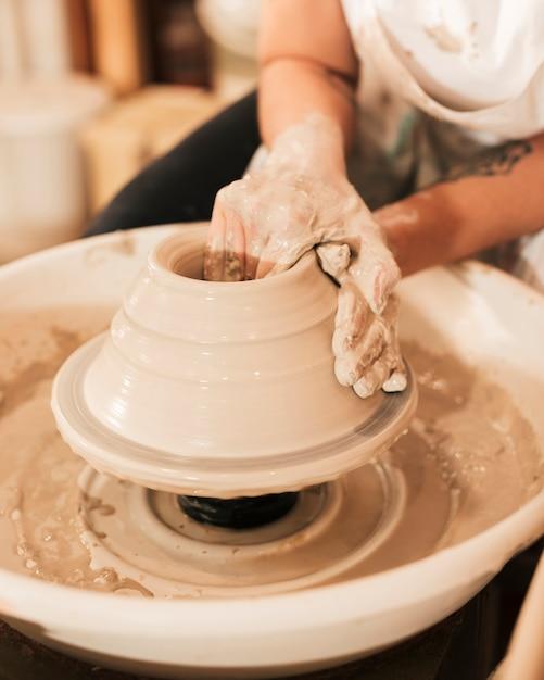 Le mani del vasaio della donna fanno sulla ruota delle terraglie Foto Gratuite