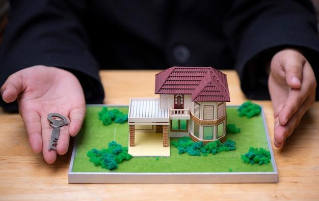 Le mani del venditore di casa stanno presentando la casa modello Foto Premium