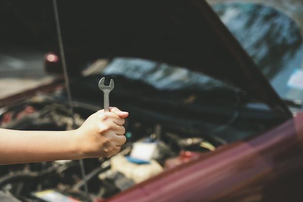 Le mani dell'ingegnere meccanico aprono la gonna della macchina per controllare il livello dell'olio della macchina. Foto Premium