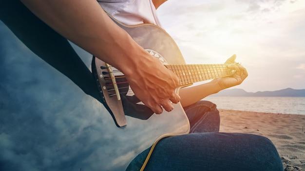 Le mani dell'uomo che giocano la chitarra acustica sulla spiaggia Foto Premium